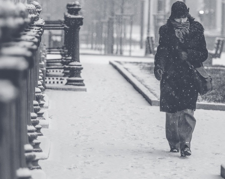 Woman wearing coat hat and scarf against freezing cold walking alone down snowy street in blizzard
